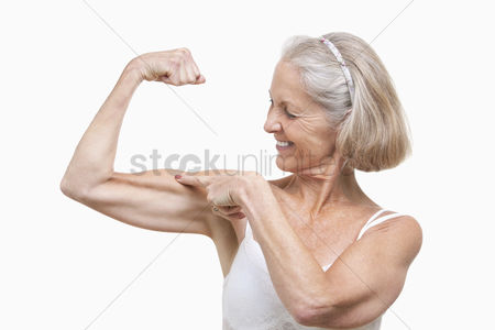 Smiling : Senior woman flexing muscles against white background