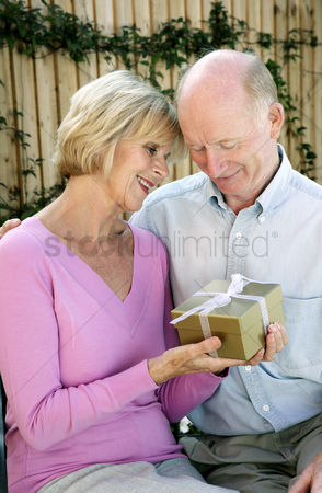 Aging process : Senior woman getting a present from her husband