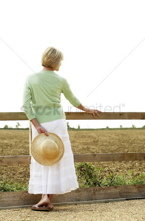 Pensive : Senior woman holding a hat on her back