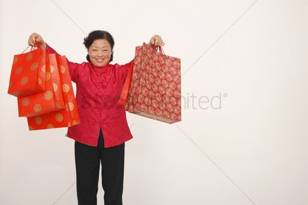 Traditional clothing : Senior woman holding up shopping bags