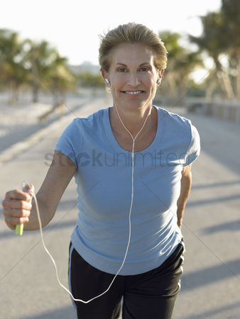 Retirement : Senior woman jogging holding mp3 player