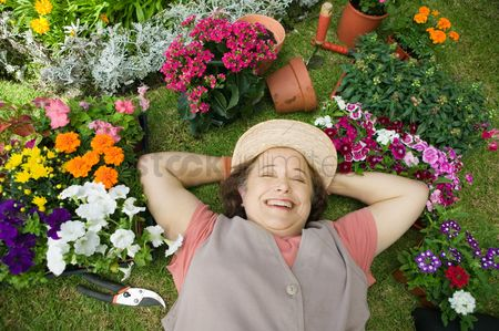 Retirement : Senior woman lying on ground among flowers smiling  overhead view