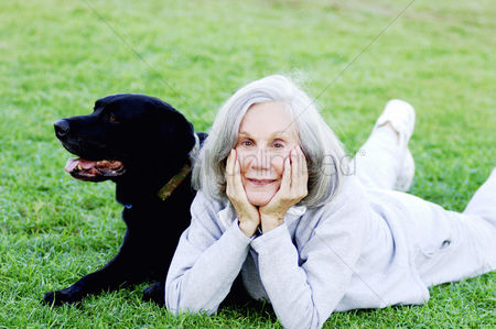 Friends : Senior woman lying on the field with her dog
