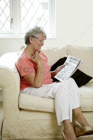 Bespectacled : Senior woman playing with crossword puzzle