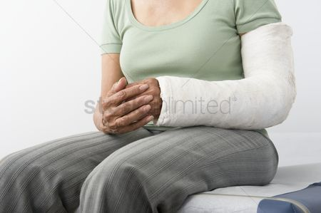 Examination : Senior woman sits with plastercast on broken arm mid-section