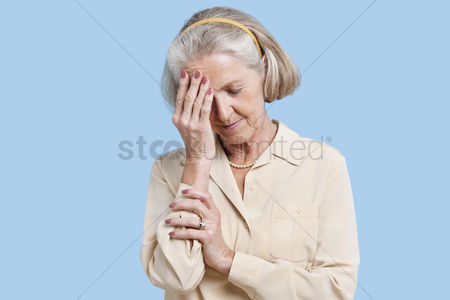 Pain : Senior woman suffering from headache against blue background