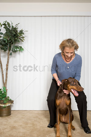 Houseplant : Senior woman with pet doberman