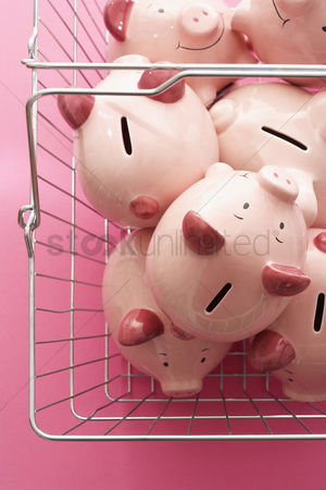 Shopping background : Shopping cart with piggy banks on pink background view from above