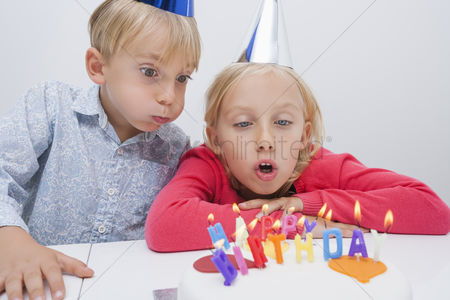 Blowing : Siblings blowing birthday candles at table