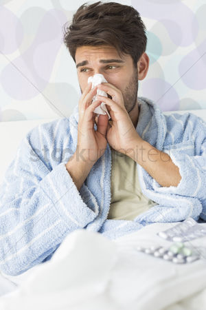 Medication : Sick man blowing his nose in tissue paper on bed at home