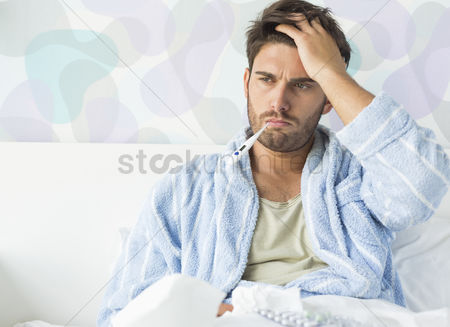 Thermometer : Sick man with thermometer in mouth sitting on bed at home