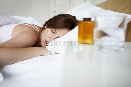 Medication : Sick woman in bed by pills on bedside table