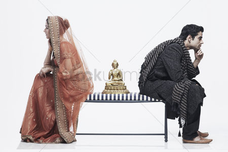 Ignorance : Side profile of a newlywed couple sitting on opposite ends of a bench with a statue of buddha between them