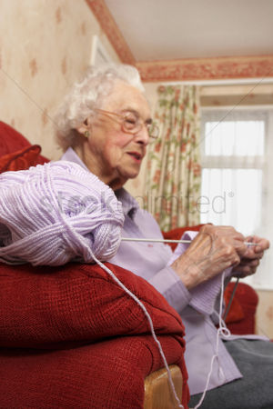 Bespectacled : Side shot of an old bespectacled lady sitting on the couch knitting