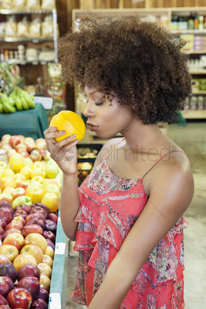 Supermarket : Side view of african american woman smelling fresh orange at supermarket