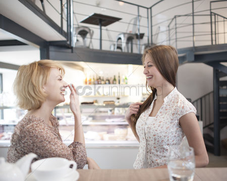 Czech republic : Side view of cheerful young women gossiping in cafe
