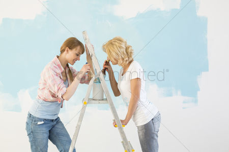 Paint brush : Side view of female friends painting together in new home