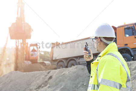 Supervisor : Side view of supervisor using walkie-talkie at construction site against clear sky