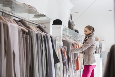 Shopping background : Side view of woman choosing sweater in store