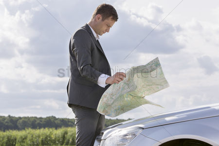 Land : Side view of young businessman reading map by car at countryside