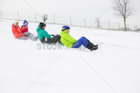 Jacket : Side view of young friends sledging on snow covered slope