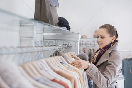 Jacket : Side view of young woman choosing sweater in store