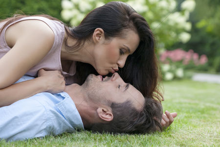 Kissing : Side view of young woman kissing man while lying in park
