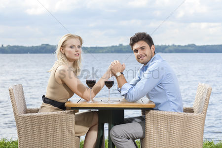Food  beverage : Side view portrait of young couple holding hands at outdoor restaurant by lake