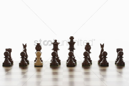 Individuality : Single white pawn in initial line up of black chess pieces