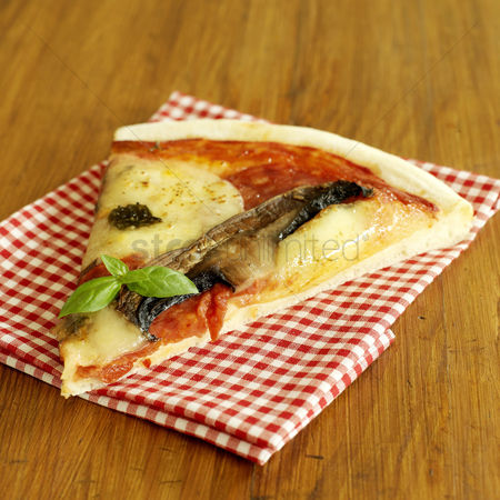 Indulgence : Slice of cooked pizza on gingham red napkin
