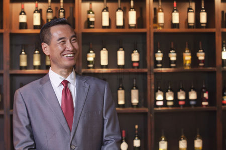 Wine bottle : Smiling businessman standing by wine bottles