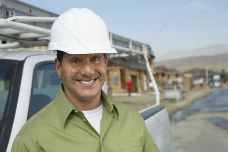 Truck : Smiling construction worker in hard hat standing next to truck on construction site