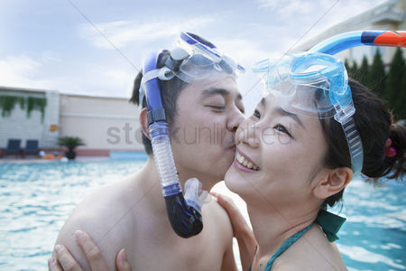 Kissing : Smiling couple kissing on the cheek wearing snorkeling gear in the pool