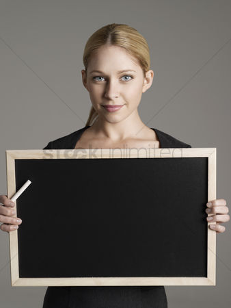 Knowledge : Smiling female teacher holding blackboard and chalk portrait