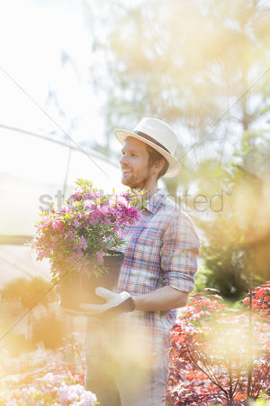 Greenhouse : Smiling gardener looking away while holding flower pot outside greenhouse