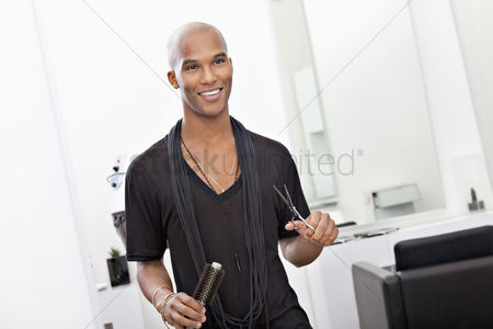 Bald : Smiling male hairdresser holding scissor and hairbrush