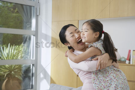 Interior : Smiling woman hugging her daughter in living room