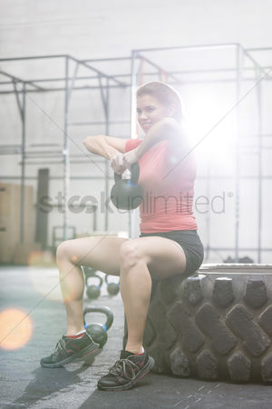 Muscle training : Smiling woman lifting kettlebell while sitting on tire at crossfit gym