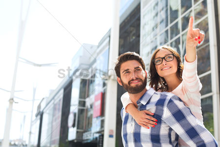 Arm raised : Smiling woman pointing away while enjoying piggyback ride on man in city