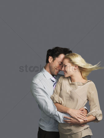 Blowing : Smiling young couple embracing hair blowing in breeze