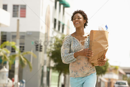 Shopping : Smiling young woman carrying groceries portrait