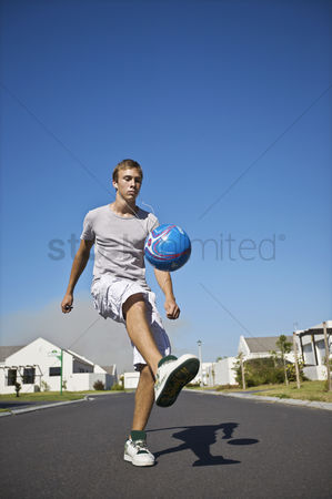On the road : South africa cape town teenage boy kicking ball on street