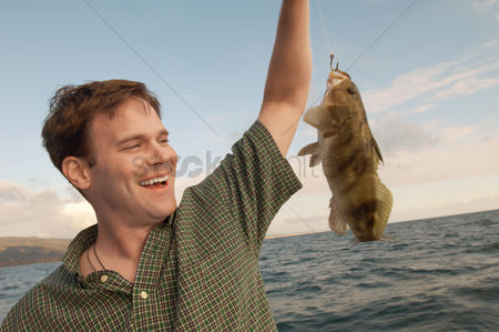 Arm raised : Sport fisherman with fish at sea