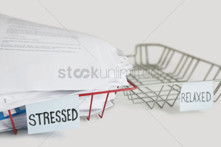 Pile : Stack of paperwork in stressed tray with empty relaxed platter over white background