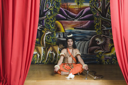 God : Stage artist dressed-up as rama and praying