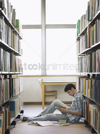 Young boy : Student reading sitting on floor in library