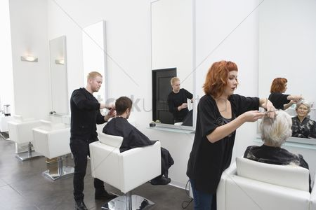 Senior women : Stylists cut clients  hair in unisex salon