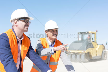 Supervisor : Supervisor explaining plan to colleague at construction site against clear sky