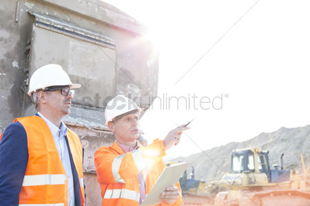 Supervisor : Supervisor showing something to colleague at construction site on sunny day