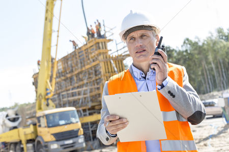 Supervisor : Supervisor using walkie-talkie while holding clipboard at construction site